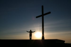 Sun setting with cross and with person standing next to cross