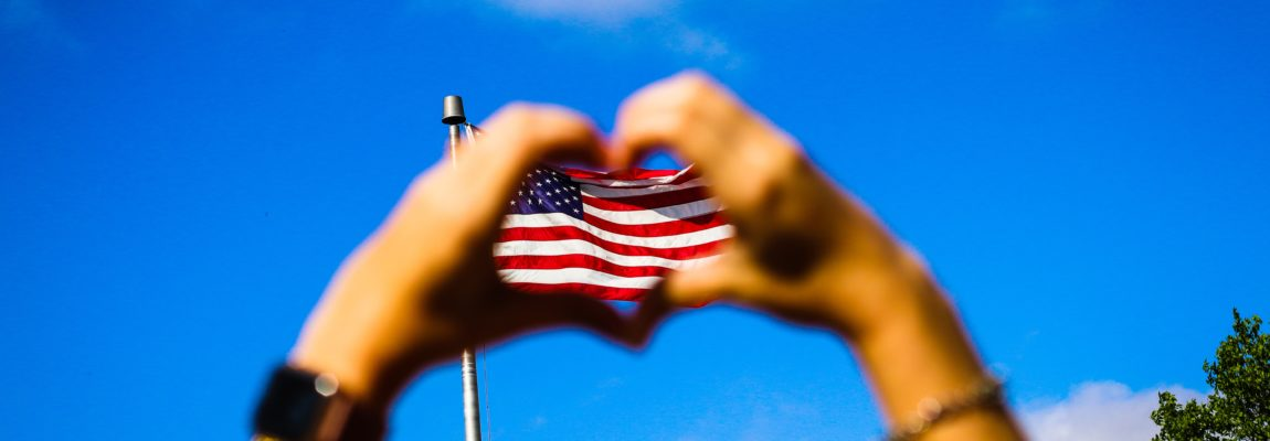 Hands making heart sign on American flag